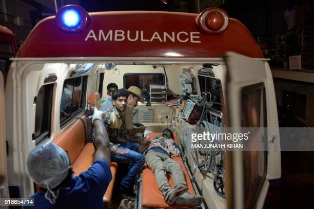 Rescue workers take care of an injured man inside an ambulance at the site where a fivestorey under construction building collapsed in Bangalore on...