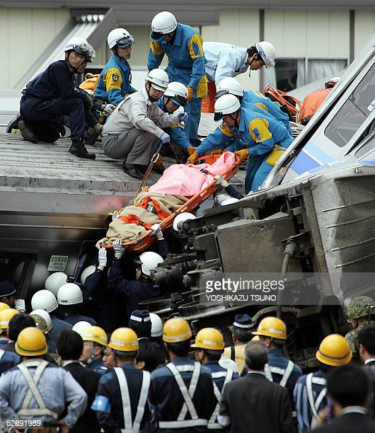 Rescue workers take out an injured on a stretcher from the site of train crash at Amagasaki city near Osaka western Japan 25 April 2005 At least 43...