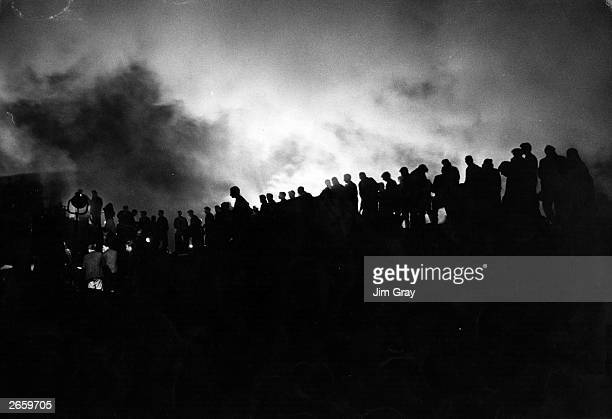Rescue workers toil into the night under floodlights at the Welsh mining village of Aberfan after a landslide buried the local school killing over...
