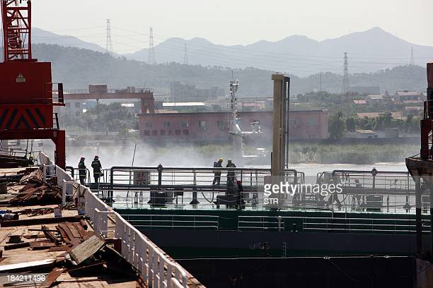 Rescue workers try to put out the fire on a 300tonne oil tanker which exploded and caught fire at the Zhangjianqi shipyard in Ningbo east China's...