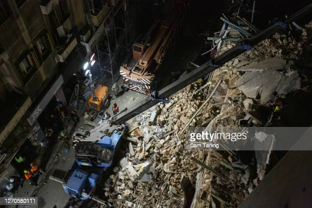 Rescue workers use a crane to lift concrete slabs from a destroyed building as they search for survivors on September 4, 2020 in Beirut, Lebanon. A...