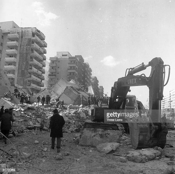 Rescue workers use a digger to sift through the remains of a block of flats after an earthquake in Bucharest which resulted in the loss of over 1500...