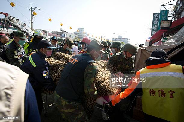 Rescue workers use a stretcher to take a victim to an ambulance found in the rubble at the Weikuan apartment complex on the second day of rescue...