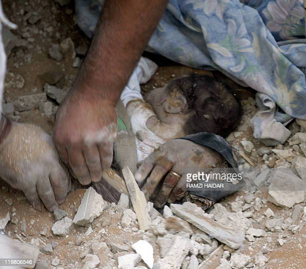Rescue workers use their bare hands to remove the dead body of ten dayold Lebanese baby Waad liying in her mother's arms 08 August 2006 in the rubble...