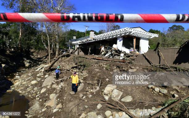 Rescue workers walk amid the debris of damaged property from mudflows carrying boulders rocks and uprooted trees in Montecito California on January...