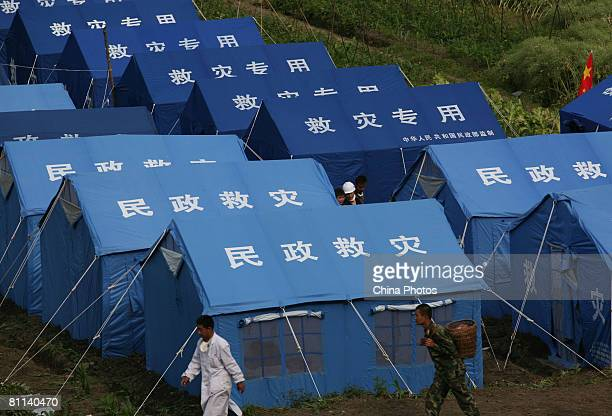 Rescue workers walk by tents to hold earthquake victims at the Hongbai Township on May 18, 2008 in Shifang of Sichuan Province, China. A major...