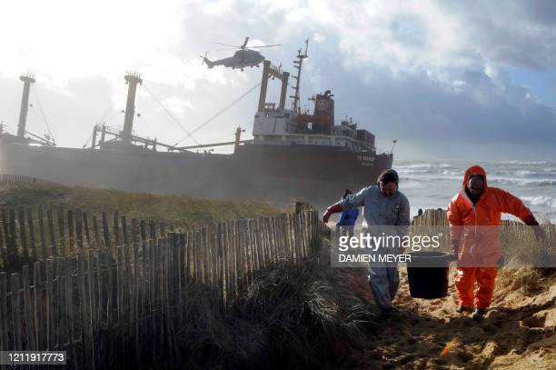 Rescue workers walk next to TK Bremen cargo ship which ran aground spilling oil off the coast of France's northwestern region of Brittany and lies...