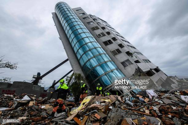TOPSHOT Rescue workers walk out from the Yun Tsui building which is leaning at a precarious angle in the Taiwanese city of Hualien on February 8 2018...