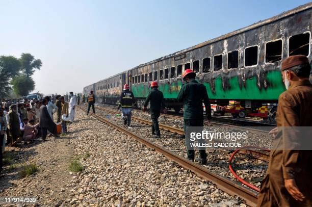 TOPSHOT Rescue workers walk past burntout train carriages after a passenger train caught on fire near Rahim Yar Khan in Punjab province on October 31...