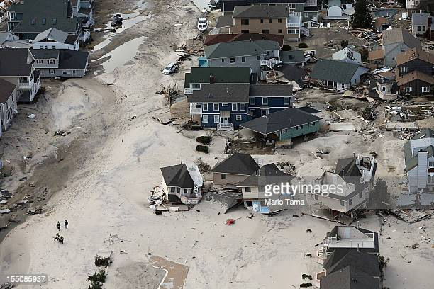 Rescue workers walk past homes wrecked by Superstorm Sandy on October 31 2012 in Seaside Heights New Jersey At least 50 people were reportedly killed...