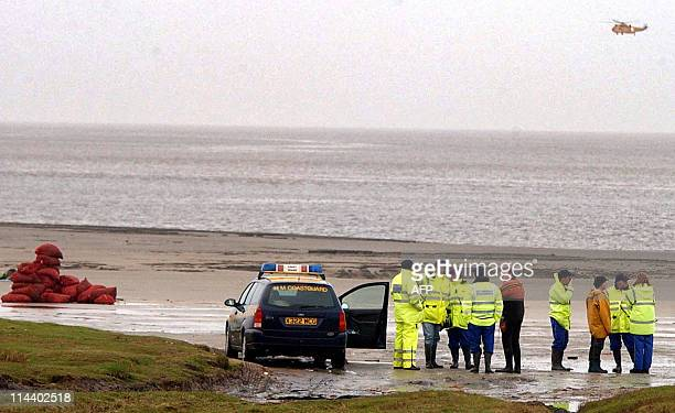 Rescue workers watch a helicopter search for more bodies where 18 Chinese cockle pickers drowned overnight trapped by the rising tide in Morecambe...