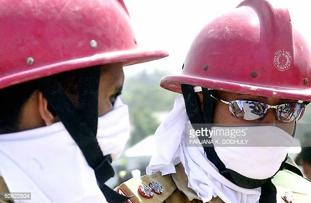 Rescue workers wear protective cloths to protect themselves from the smell of decomposing bodies after a factory collapsed 11 April in Palash Bari,...