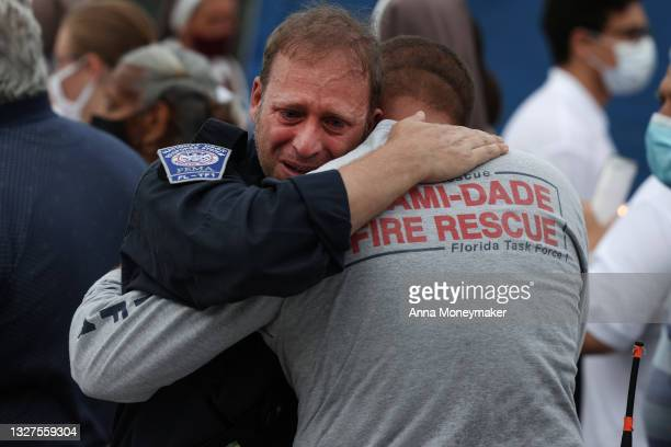 Rescue workers with the Miami Dade Fire Rescue embrace after a moment of silence near the memorial site for victims of the collapsed 12-story...