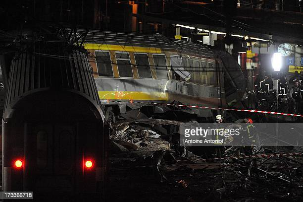 Rescue workers work alongside a derailed carriage after a train accident on July 12 2013 in BretignysurOrge France An intercity train carrying 385...