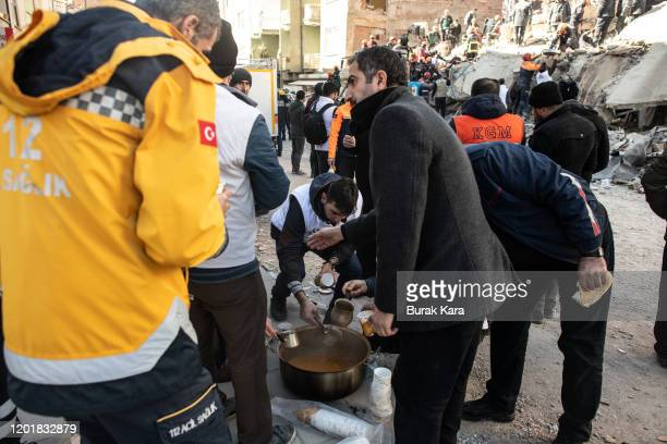 Rescue workers work at the scene of a collapsed building as aid workers give soup to them on January 25 2020 in Elazig Turkey The 68magnitude...