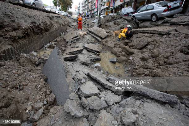 Rescue workers work in the damaged road after gas explosions in southern Kaohsiung on August 1, 2014 in Kaohsiung, Taiwan. A series of powerful gas...