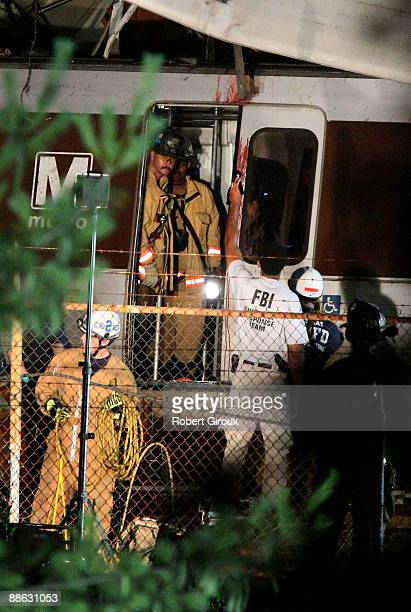 Rescue workers work through the night at the site of two Red Line Metrorail trains that collided with one another between the Fort Totten and Takoma...