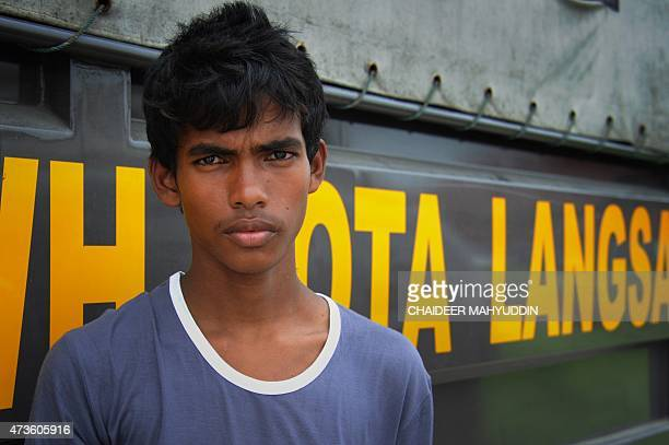 Rescued 14 year old Bangladeshi Absaruddin stands alongside an Indonesian police truck at the new confinement area in the fishing town of Kuala...