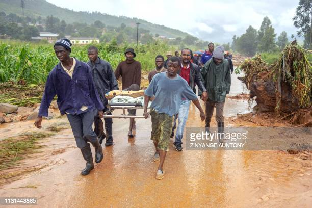 A rescued man is seen carried on a stretcher bed by friends on March 18 in Ngangu township Chimanimani eastern Zimbabwe after the area was hit by the...