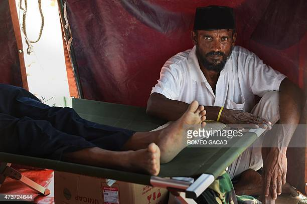 A rescued migrant from Bangladesh watches over another migrant receiving medical attention at the confinement area in the fishing port of Kuala...