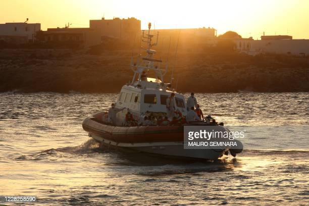 """Rescued migrants are being transfered at the commercial port of Lampedusa on August 29, 2020 from the Coast Guard patrol boat """"CP-319"""", which..."""