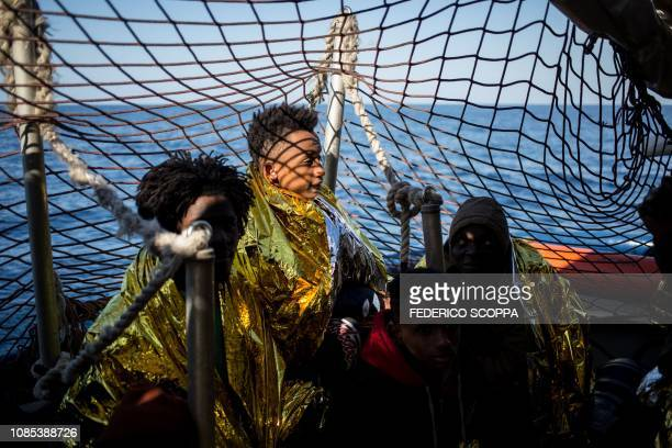Rescued migrants from a group of 47 wrapped in survival blankets and including an underaged are pictured aboard the Dutchflagged vessel Sea Watch 3...
