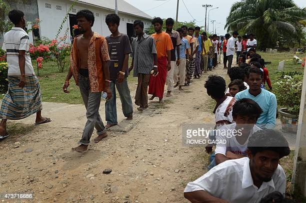 Rescued migrants from Bangladesh walk in rows as they prepare for an identification process by Indonesian authorities and the International...