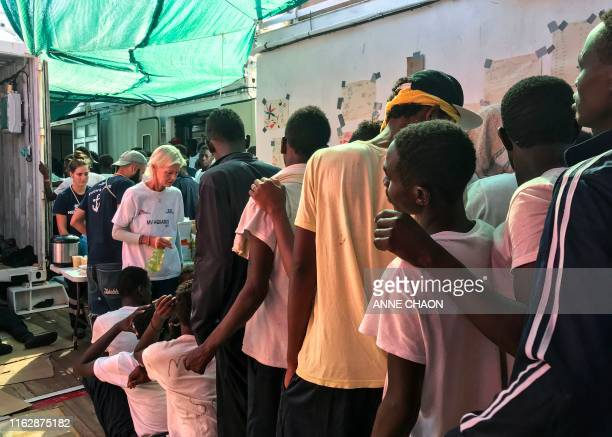 Rescued migrants queue to receive food aboard the 'Ocean Viking' rescue ship jointly operated by French NGOs SOS Mediterranee and Medecins sans...