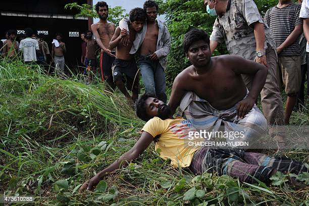 Rescued migrants wait for an ambulance upon their arrival at the new confinement area in the fishing town of Kuala Langsa in Aceh province on May 15...