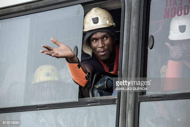 TOPSHOT A rescued miner gestures out a bus window carrying some of the hundreds of miners rescued from the Beatrix gold mine shaft number 3 where...