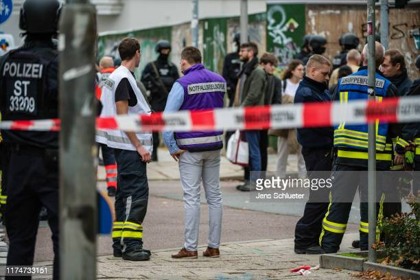 Rescued parishioners of the Jewish community and police forces stand near the scene of a shooting that has left two people dead on October 9 2019 in...