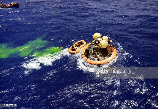 Rescuemen approach the Apollo 12 spacecraft during recovery operations following a safe splashdown approximately 350 nautical miles southeast of...