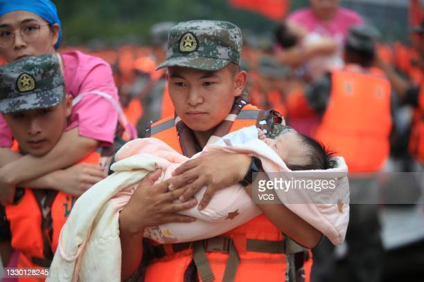 Rescuer carries a baby at flooded Fuwai Central China Cardiovascular Hospital after the torrential rains, on July 22, 2021 in Zhengzhou, Henan...
