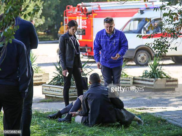 TOPSHOT A rescuer carries an injured victim of a blast at a college in the city of Kerch on October 17 2018 At least 18 people died in a blast in a...
