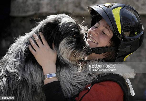 Rescuer congratulates her dog as they search for survivors in the remains of a collapsed building on April 8, 2009 in the Abruzzo capital L'Aquila....