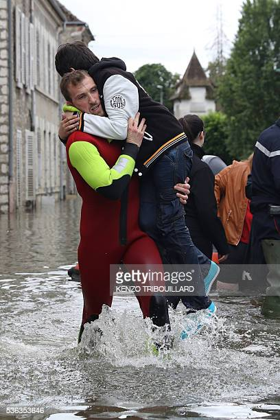 A rescuer evacuates a boy accross a flooded street on June 1 2016 in SouppessurLoing southeast of Paris Torrential downpours have lashed parts of...