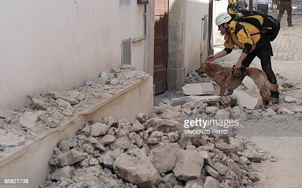 Rescuer follows his dog on April 6, 2009 at the entrance of a house which partly collapsed in Onna, a small town some 10 kilometers from L'Aquila,...