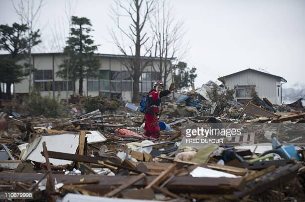 A rescuer from the Mexican Red Cross indicates the location of a dead body in Sendai on March 16 2011 days after a massive earthquake and tsunami...