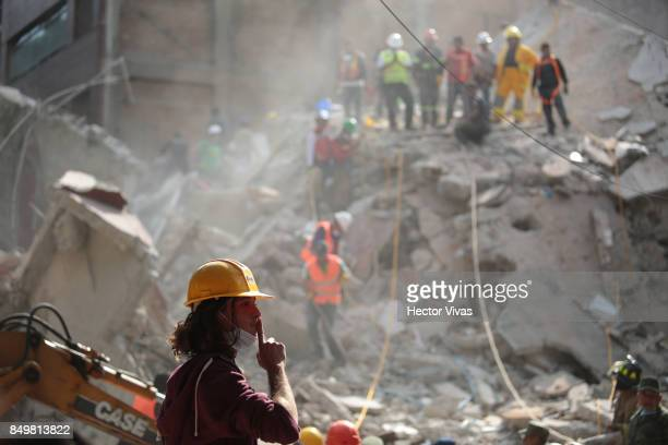 A rescuer gestures as he looks for victims amid the ruins of a building knocked down by a magnitude 71 earthquake that jolted central Mexico damaging...