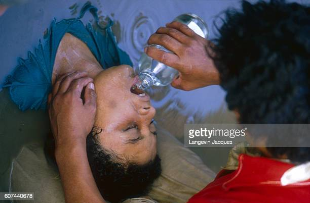 Rescuer gives fresh water to a child who was caught in a lahar as it flowed from the erupting Nevado del Ruiz volcano in Colombia. The 1985 eruption...