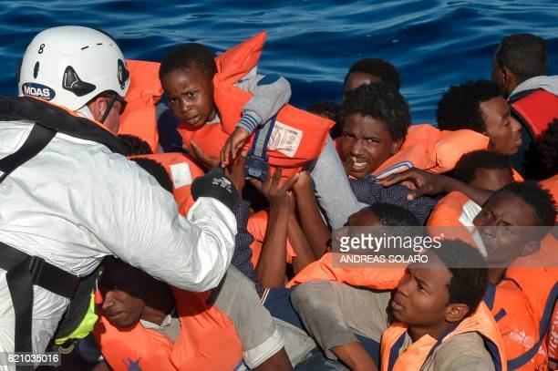 Rescuer grabs a child among the migrants and refugees seated on a rubber boat during a rescue operation of the Topaz Responder, a rescue ship run by...