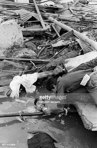 Rescuer helps a child who was caught in a lahar as it flowed from the erupting Nevado del Ruiz volcano in Colombia. The 1985 eruption completely...