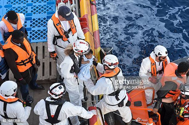 A rescuer holds a baby as migrants and refugees are transferred from the Topaz Responder a ship run by Maltese NGO Moas and the Italian Red Cross to...