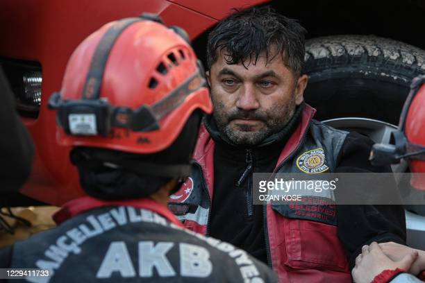 Rescuer reacts as he rests during the ongoing search operation at the site of a collapsed building as they look for survivors and victims in the city...