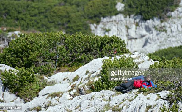 A rescuer rests near the entrance to the Riesending cave at Untersberg mountain near Marktschellenberg Germany 19 June 2014 The seriously injured...