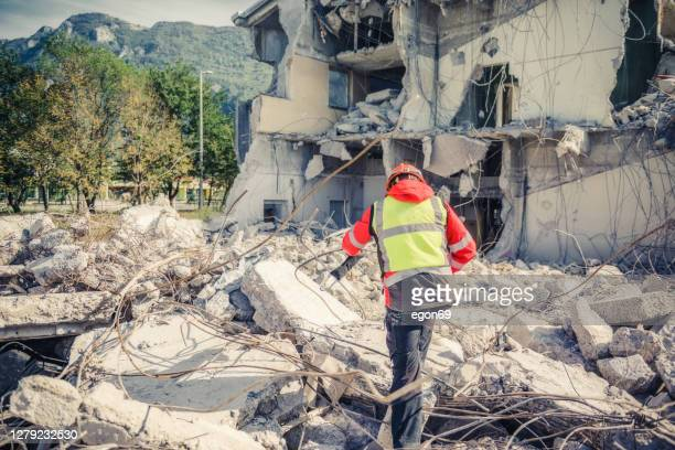 rescuer search trough ruins of building - natural disaster stock pictures, royalty-free photos & images