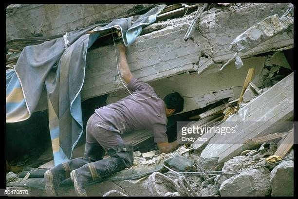 Rescuer searching through rubble in collapsed bldg after earthquake
