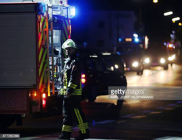 A rescuer stands on a road near railtracks in Wuerzburg southern Germany on July 18 2016 after a man attacked train passengers with an axe German...