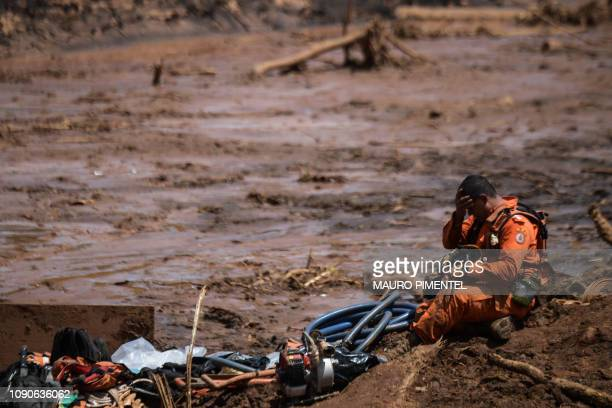 TOPSHOT A rescuer takes a break during his work in the search for victims four days after the collapse of a dam at an ironore mine belonging to...