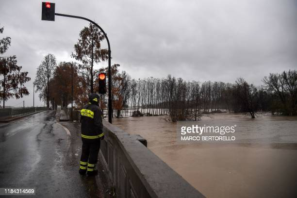 A rescuer views the Po river from a bridge in the village of Carde south of Turin after the river overflew its banks following heavy rainfall on...